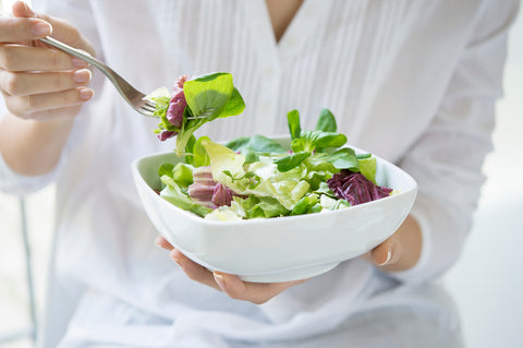 Woman eating organic green salad