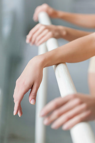 Beautiful, delicate hands drape don ballet barre
