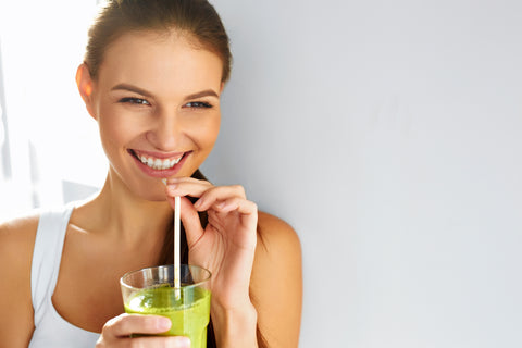 Happy brunette woman drinking organic green smoothie