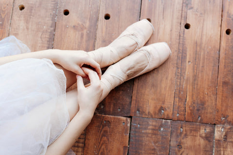 Ballerina sitting on wooden floor in ballet slippers