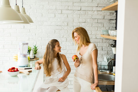 Mother and daughter cooking with organic ingredients in gorgeous kitchen