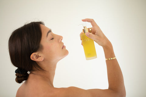 Brunette Woman Applying Liquid Gold Cleansing Face Oil
