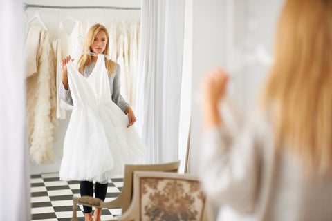 Blonde woman in light room holding up white dress, picking out outfit