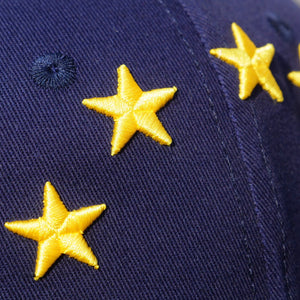 EUROPEAN Stars Cap close up from the left on wooden surface with garden background