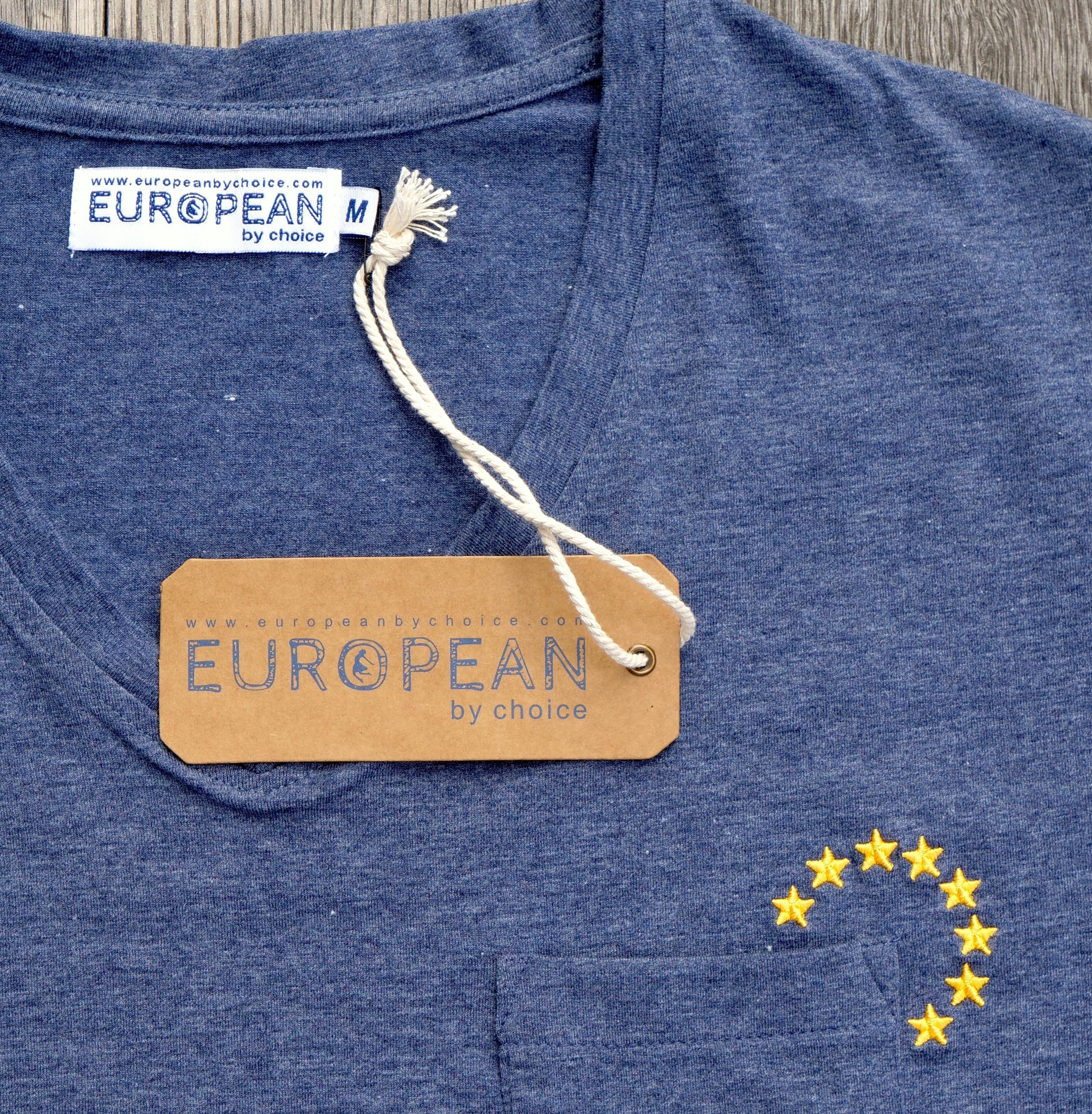 EUROPEAN T-Shirt with small stars pocketstars embroidered next to pocket UNISEX close up of stars and hangtag with neck lable label from the front with hang #europeanbychoice hangtag and neck label attached to shirt portrayed on wooden background