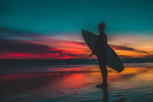 surfer on a beach at sunset | shoresurfwear.com
