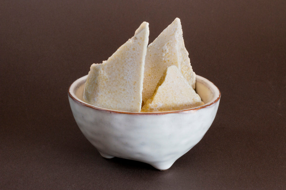 cacao butter: a small white bowl containing several pale-yellow chunks of cacao butter