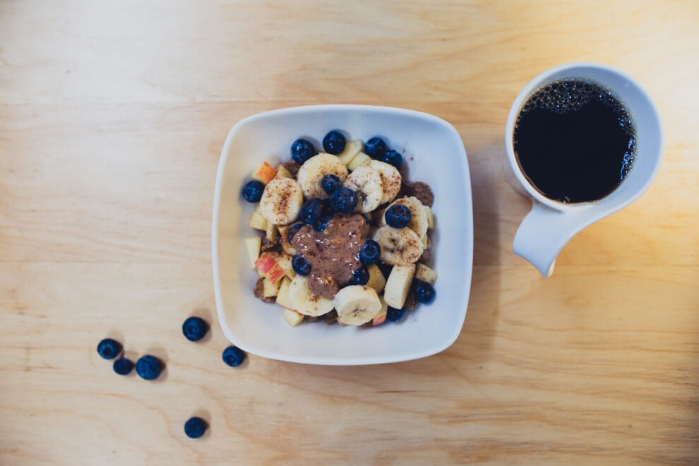 a cup of coffee alongside a plate of fruit with cacao powder and peanut butter on top