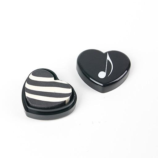 Heart shaped eraser, black, with a white treble clef or quaver.