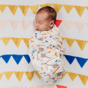 sleeping baby swaddled in a candy print blanket laying on a banners crib sheet