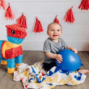 smiling baby with banners blanket playing with a balloon and pinata