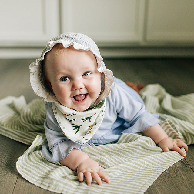 smiling baby wearing family farm reversible bandana bib with green stripe blanket