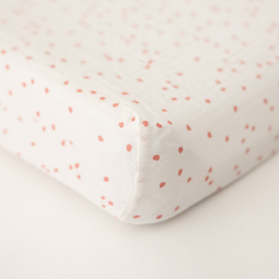 cotton muslin changing pad cover with pink cherry blossom petals on a white background