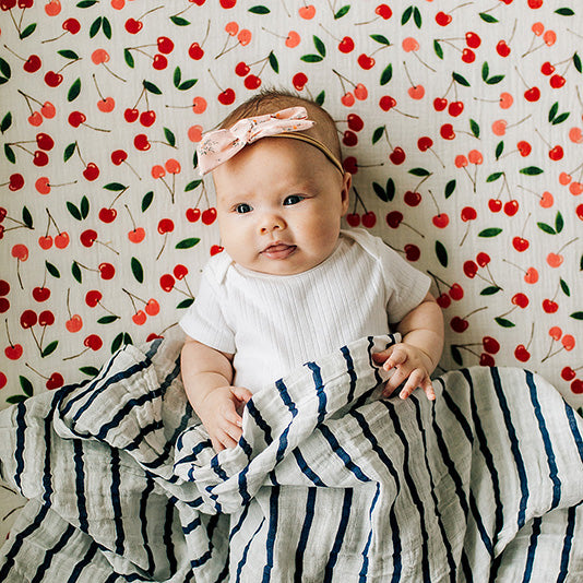 smiling baby laying on a cherries crib sheet with a navy stripe blanket draped over the baby