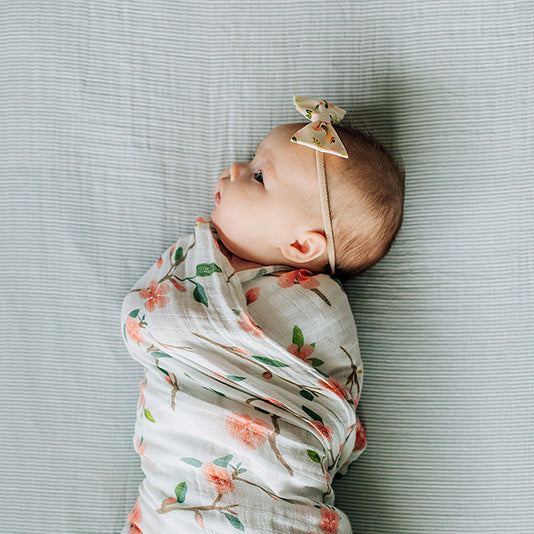 baby laying on a micro grey crib sheet swaddled in a peach blossom blanket