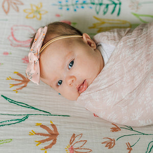 baby swaddled in a pink meadow blanket laying on a pastel petal crib sheet