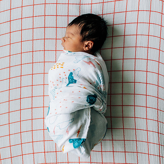 sleeping baby swaddled in a clapping clouds blanket on an orange windowpane crib sheet