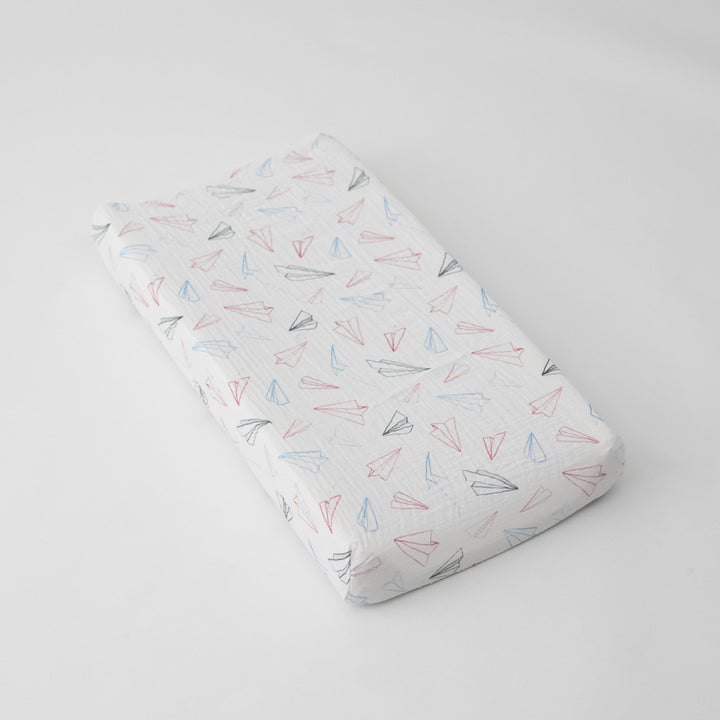 cotton muslin changing pad cover with with red, blue, and grey paper airplanes on a white background