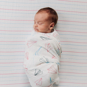 sleeping baby swaddled in a paper planes swaddle on a letter lines crib sheet