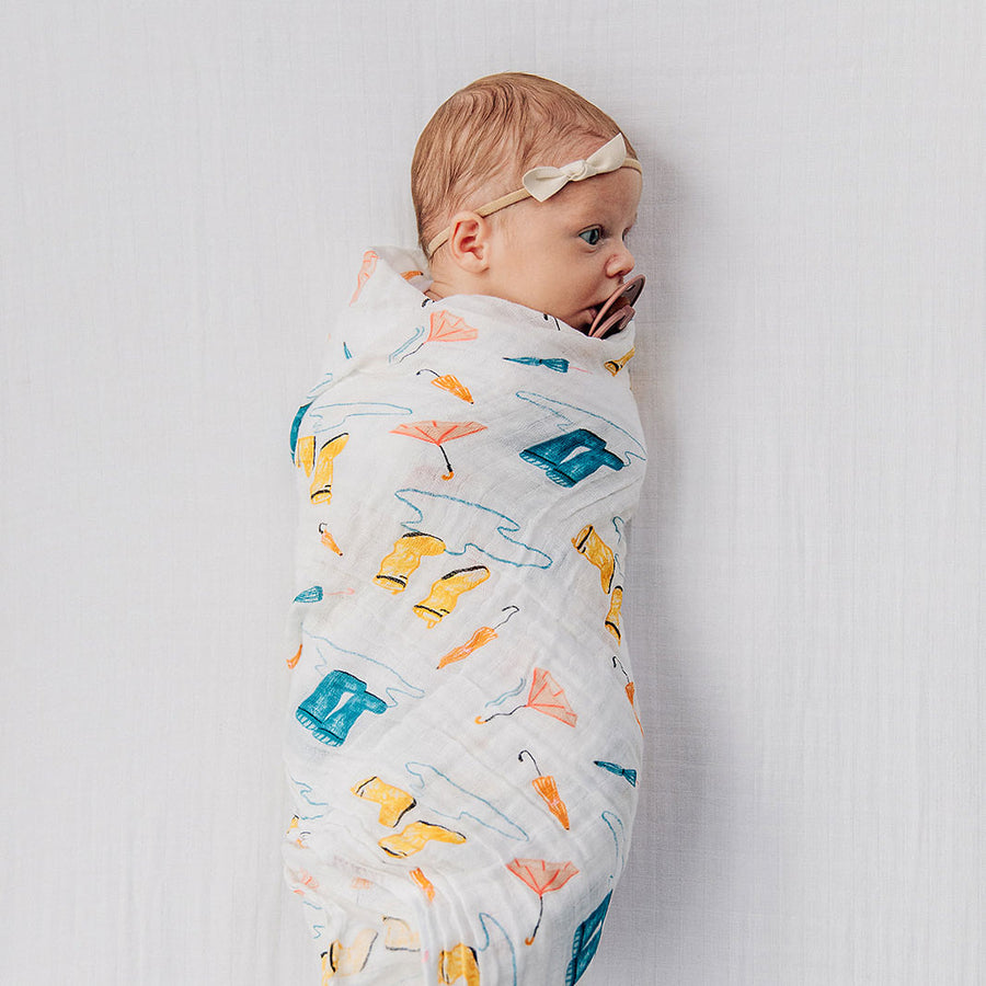 baby swaddled in a puddles blanket laying on a white crib sheet