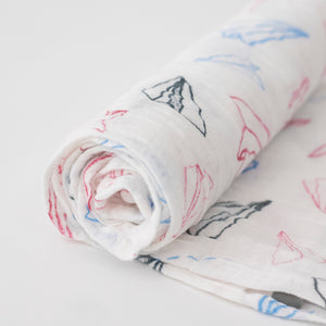 single swaddle blanket with blue, red, and grey paper planes on a white background