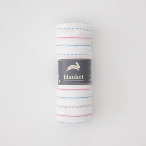 single swaddle blanket made to looking like a piece of paper with blue and red lines rolled in Red Rover packaging