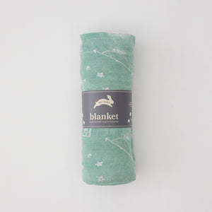 single swaddle blanket that is styled to look like a chalk board with white chalk marks and writing rolled in Red Rover packaging