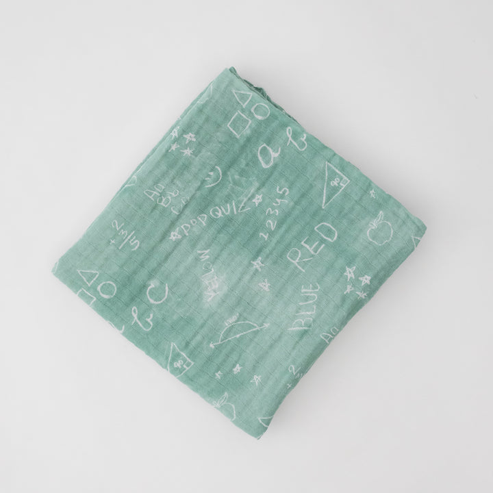 single swaddle blanket that is styled to look like a chalk board with white chalk marks and writing