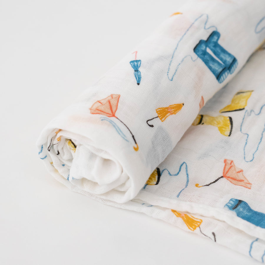single swaddle blanket with yellow and blue rain boots, puddles, and orange umbrellas on a white background