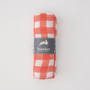single swaddle blanket in red plaid print rolled in Red Rover packaging