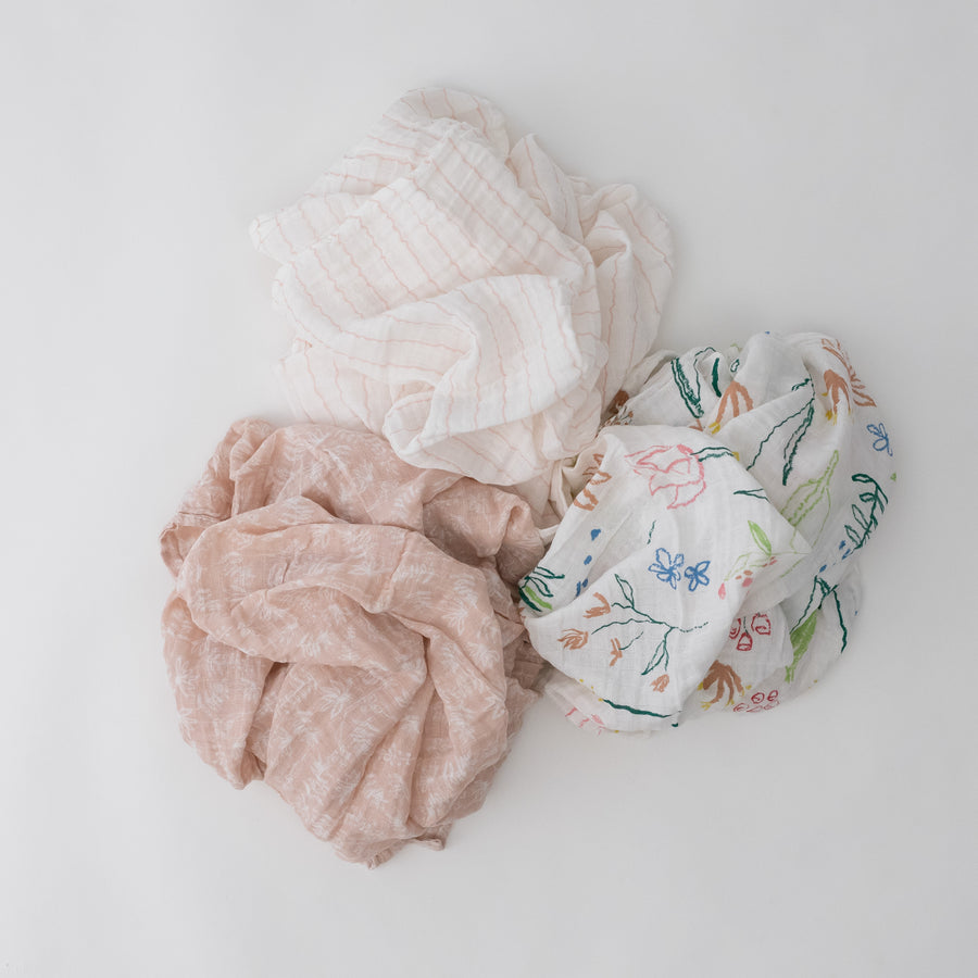 3 swaddle blankets featuring a flower, pink stripe, and pink background with white flowers print