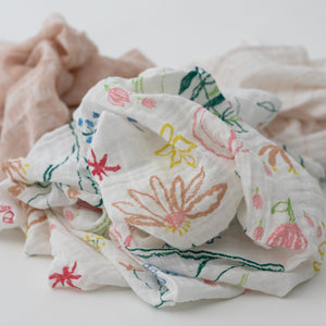 3 swaddle blankets focusing on the pastel petal print with pink, yellow, blue and red flowers