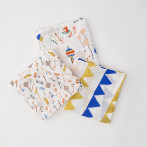 3 swaddle blankets featuring blue and yellow triangle banners, pint with different candies, and party with cake balloons and pinatas