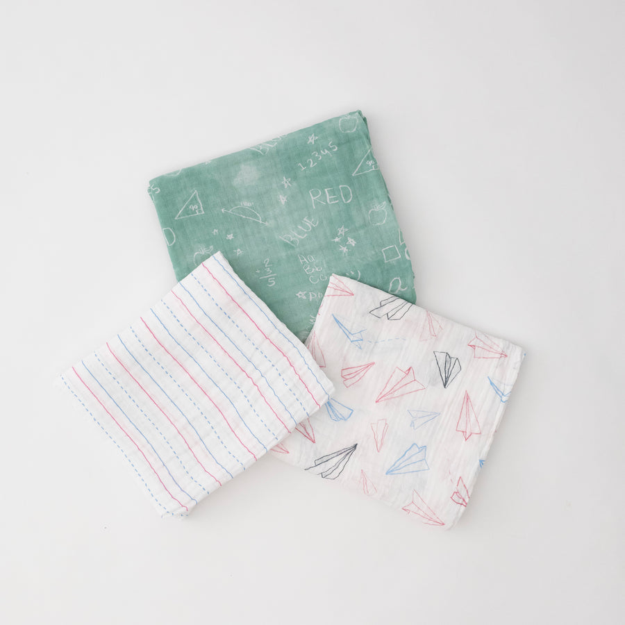 3 swaddle blankets featuring red and blue paper planes, lined paper print, and chalk board style print