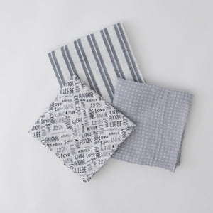 "3 swaddle blankets featuring double grey stripes with a white background, little white x's and o's on a grey background, and mesh of the word ""love"" in a bunch of different languages"