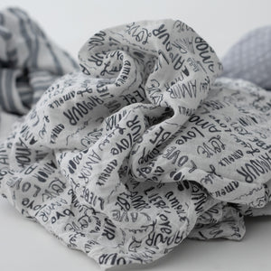 "3 swaddle blankets focusing on the love language print with the word ""love"" in multiple languages"