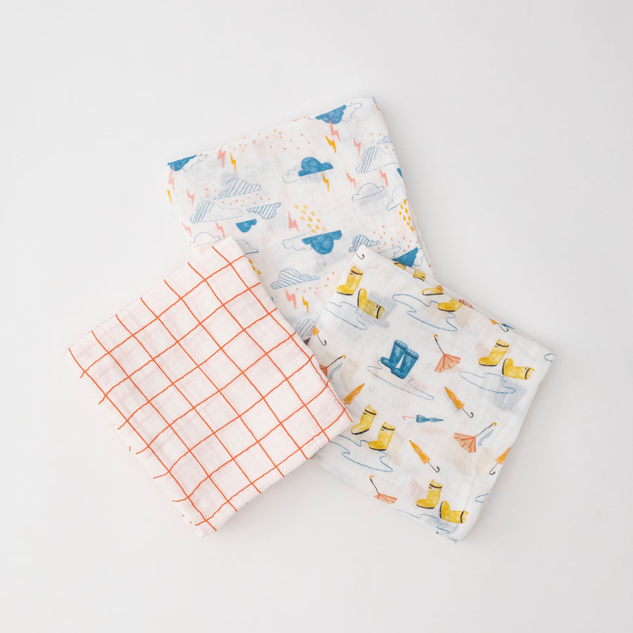 3 swaddle blankets they are orange crossing stripes, clouds with rain and lightening, and yellow rain boots with puddles and umbrellas