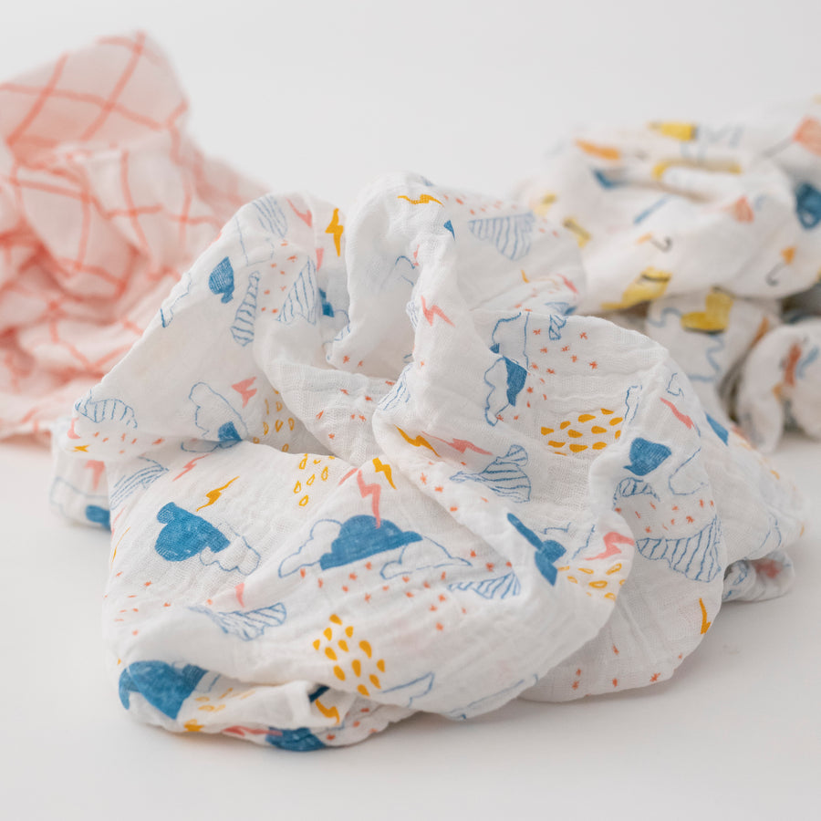 3 swaddle blankets focusing on the print with blue clouds, yellow rain and lightening