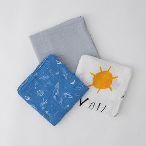 3 swaddle blankets featuring grey micro stripe, white background yellow sun and blue stars, and blue background with white space items