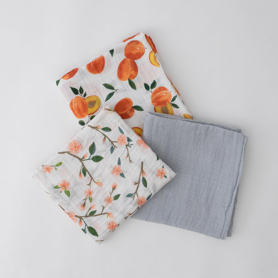 3 swaddle blankets featuring peach blossoms, whole and cut open peaches, and grey micro stripes