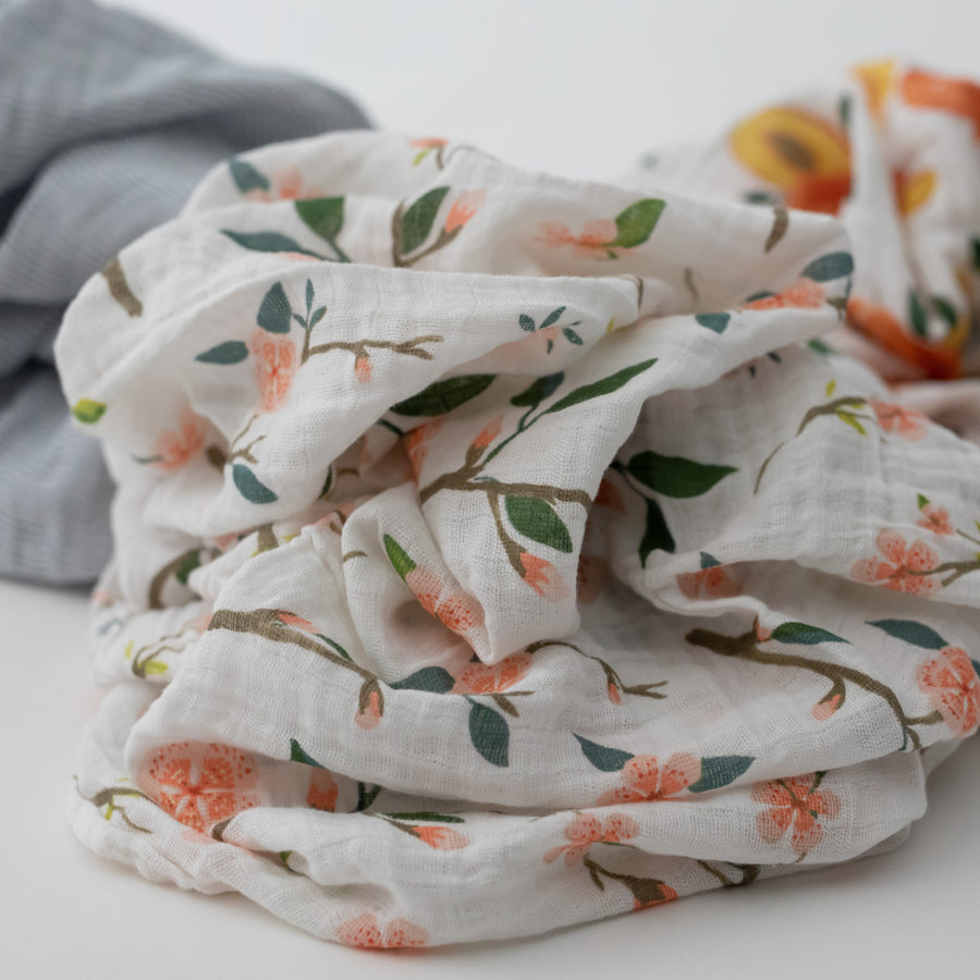 3 swaddle blankets focusing on the peach blossom print with pink flowers and white background
