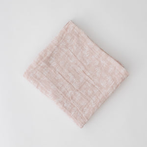 single swaddle blanket with small white flowers on a blush pink background
