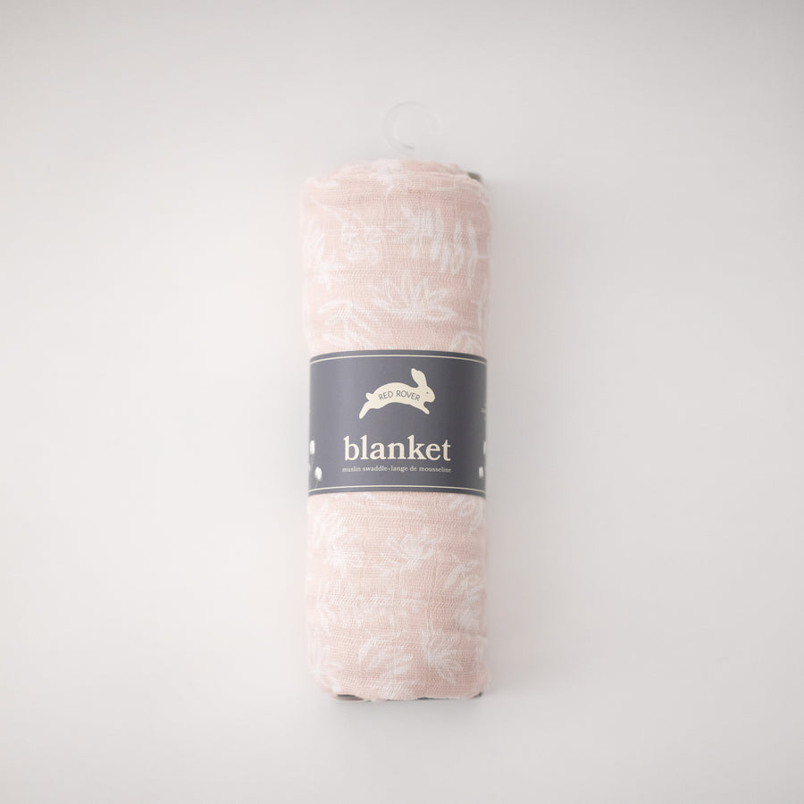 single swaddle blanket with small white flowers on a blush pink background rolled in Red Rover packaging