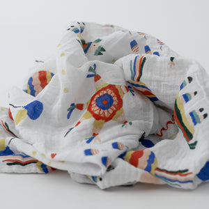 single swaddle blanket with party items including balloons, pinatas, party hats, confetti, and cake