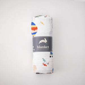 single swaddle blanket with party items including balloons, pinatas, party hats, confetti, and cake rolled in Red Rover packaging