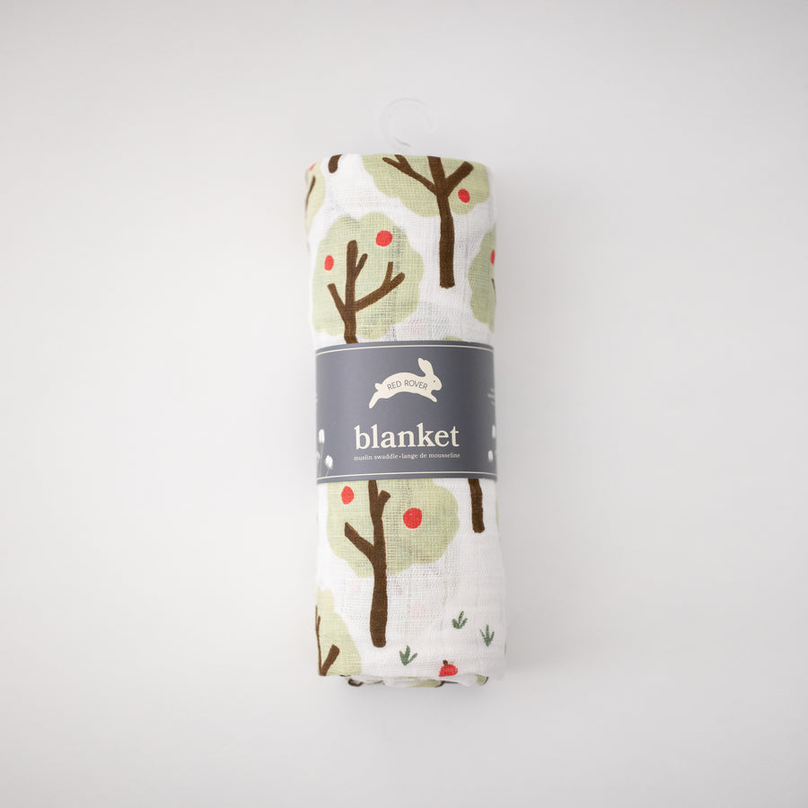 single swaddle blanket with lots of apple trees on a white background rolled in Red Rover packaging
