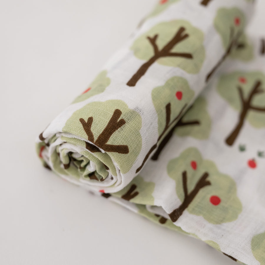 single swaddle blanket with lots of apple trees on a white background