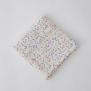 single swaddle blanket with lots of different colored sprinkles on a white background