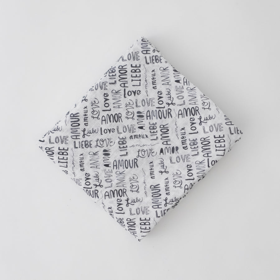 "single swaddle blanket with the word ""love"" in multiple different languages in grey writing"
