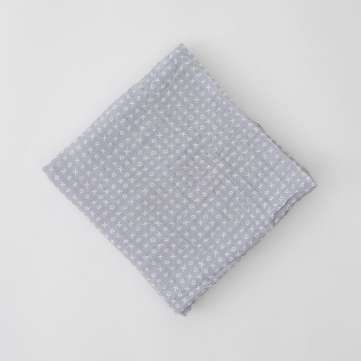 single swaddle blanket with small x's and o's on a grey background